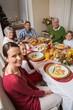 Festive family smiling at camera during christmas dinner