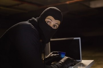 Burglar shopping online with laptop while looking at camera
