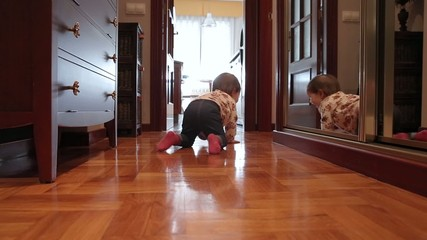 Happy baby girl crawling at floor home