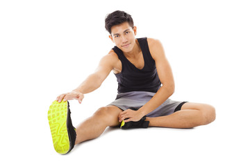 smiling young fitness man sitting and making stretching exercise