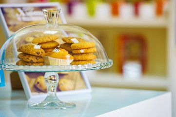 Cookies under glass cover on a white table