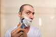 Man using a razor to shave his beard off