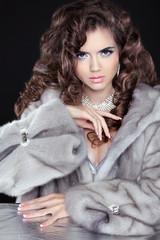 Beautiful fashion brunette girl in mink fur coat isolated on bla