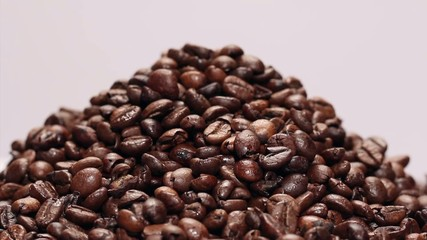 Pile of roasted coffee beans on white background,rotating