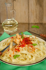 Pasta with tomato sauce on wooden table