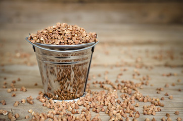Buckwheat groats in a bucket on a wooden background