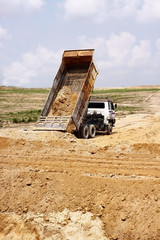 Heavy dump truck unloading soil at a construction site