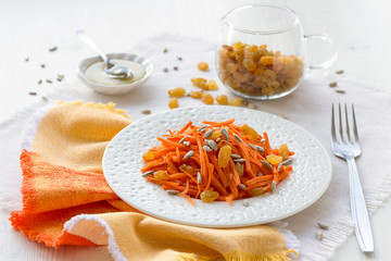 Carrot salad with raisins, sunflower seeds and honey. Copy space