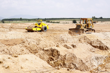 Bulldozer and Soil Compactor at Construction Site