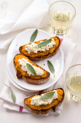 Bruschetta with pumpkin puree, ricotta and sage on a white plate