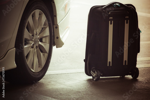 suitcase near a taxi - 73670593