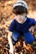 Little boy in cap squat outdoor in park