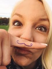 Frau macht Spaß mit Schnurrbart