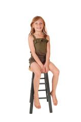 Girl sitting on high chair.