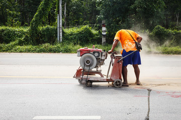 Cutting asphalt road for repair by hydraulic driven angle grinde