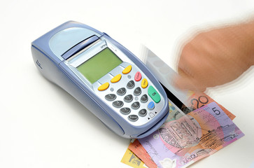 EFTPOS machine with credit cards and Australian money.