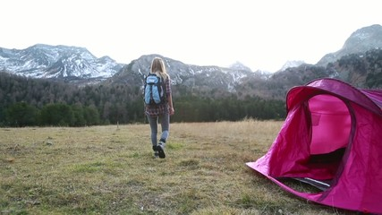 Hiker returns to tent, outstretches arms