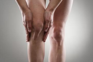 Woman touching her injured knee. Rheumatism or arthrosis.