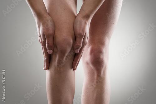 Woman touching her injured knee. Rheumatism or arthrosis. - 73674584