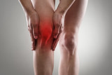 Tendon problems on woman's leg indicated with red spot. - 73674722