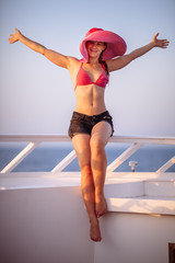 Young woman in pink sunhat on cruise ship deck looking at camera