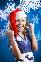 Young beautiful woman in Santa hat is looking at camera smiling.