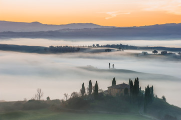 Fantastic Tuscan landscape in the fog and the light of the risin