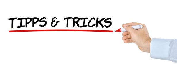 Hand mit Stift schreibt Tipps und Tricks