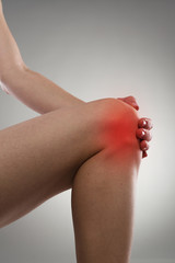 Woman touching her knee in pain. Gout or arthritis concept.