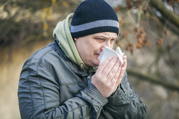 Man with napkin near nose at outdoors on the bench