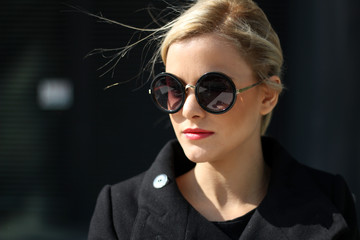 A portrait of a beautiful blond with sunglasses, outside