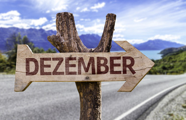 December (In German) sign with a road background