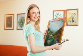 Happy woman hanging the art picture