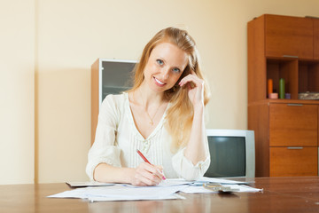 smiling blonde woman fills in documents