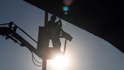 Silhouette Worker In Bucket of Mobile Crane