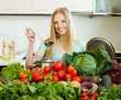 long-haired woman cooking with heap of raw vegetables