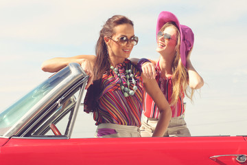 Beautiful ladies with sun glasses posing in a vintage car
