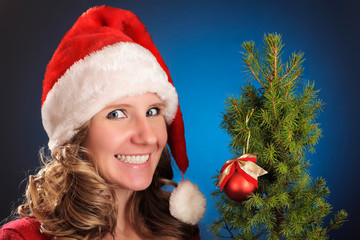 Young woman in red Santa hat with a small Christmas tree