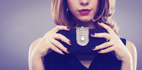 Beautiful young woman with a black clutch in hand.