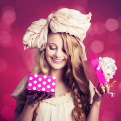 Portrait of a girl doll with gift box on pink background.