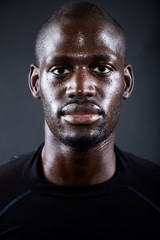 Athletic man running in black background.