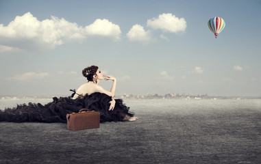 girl in a luxurious dress with a suitcase dreaming