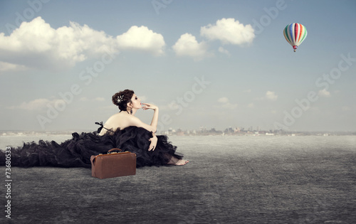 Leinwandbild Motiv girl in a luxurious dress with a suitcase dreaming