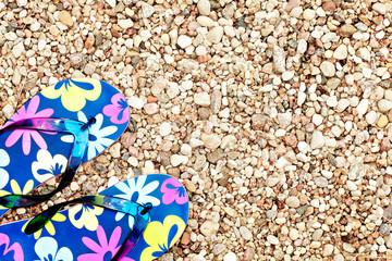 Colorful flip flops on beach pebbles