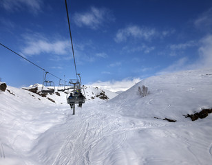 Chair-lift and off-piste slope in sun day