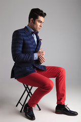 young casual man sitting on a stool