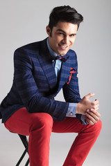 Happy young fashion man sitting on a stool