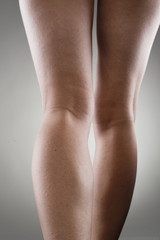 Woman's leg calves over grey. Muscular hurt concept.