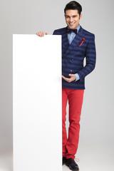 casual fashion man presenting a white empty board.