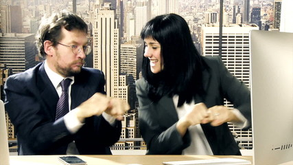 Business man and woman dancing in office